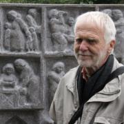 Skulptören Sam Westerholm framför minnesstenen över Maria Sandel